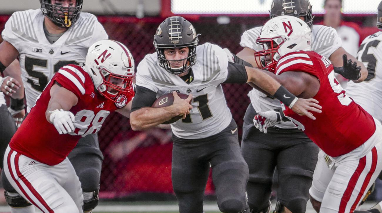Purdue quarterback David Blough (11) scrambles between Nebraska defensive tackle Kevin Maurice (55) and defensive end Ross Dzuris, left, during the second half of an NCAA college football game in Lincoln, Neb., Saturday, Oct. 22, 2016. (AP Photo/Nati Harn