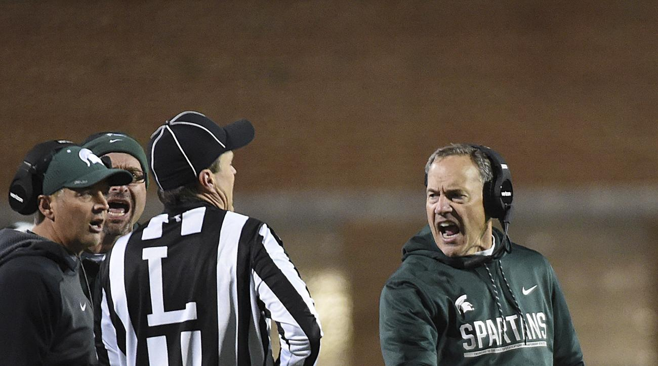 Michigan State head coach Mark Dantonio, right, reacts to a penalty in the first half in an NCAA college football game against Maryland, Saturday, Oct. 22, 2016, in College Park, Md. (AP Photo/Gail Burton)