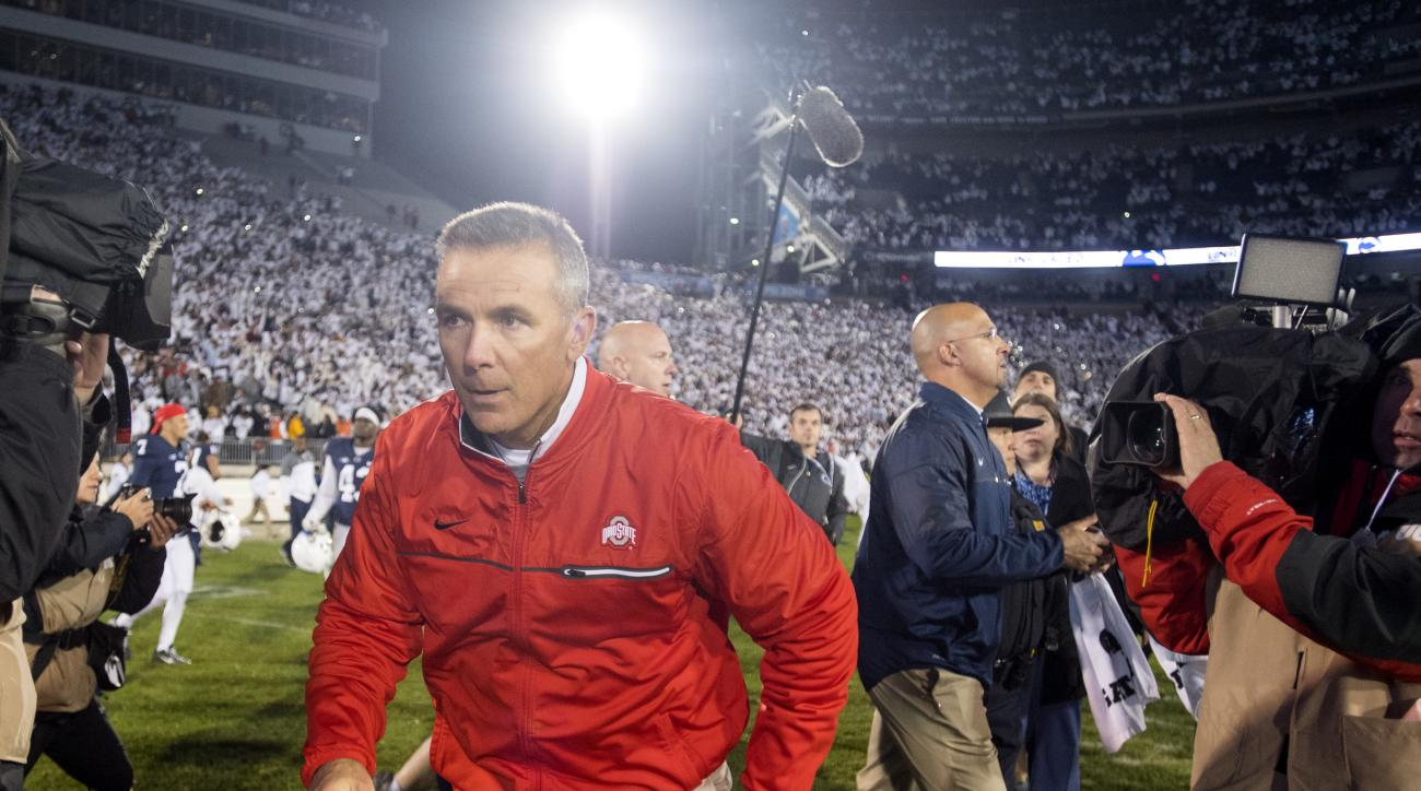 Ohio State coach Urban Meyer runs off the field after shaking hands with Penn State coach James Franklin, background, after an NCAA college football game Saturday, Oct. 22, 2016, in State College, Pa. Penn State won 24-21. (Abby Drey/Centre Daily Times vi