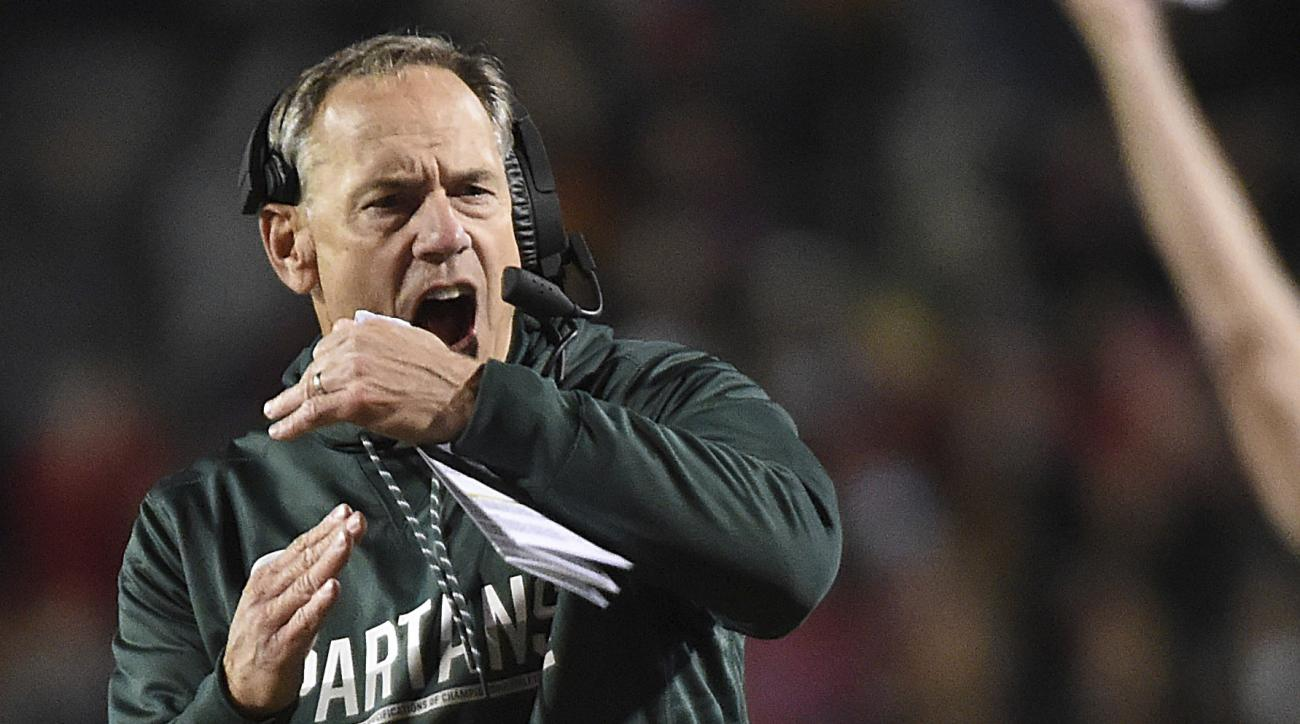 FILE - In this Oct. 22, 2016, file photo, Michigan State's Mark Dantonio calls for a timeout against Maryland in the first half of an NCAA college football game, in College Park, Md. Michigan State used to be at its best at the end of games, making plays