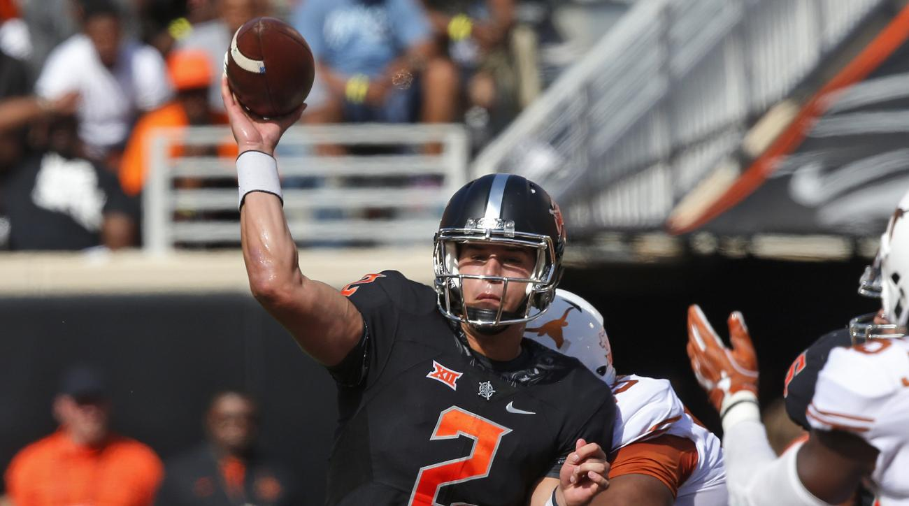 FILE - In this Oct. 1, 2016, file photo, Oklahoma State quarterback Mason Rudolph (2) throws as he is hit by Texas defensive tackle Paul Boyette Jr. (93) in the first quarter of an NCAA college football game in Stillwater, Okla. Rudolph is the third strai