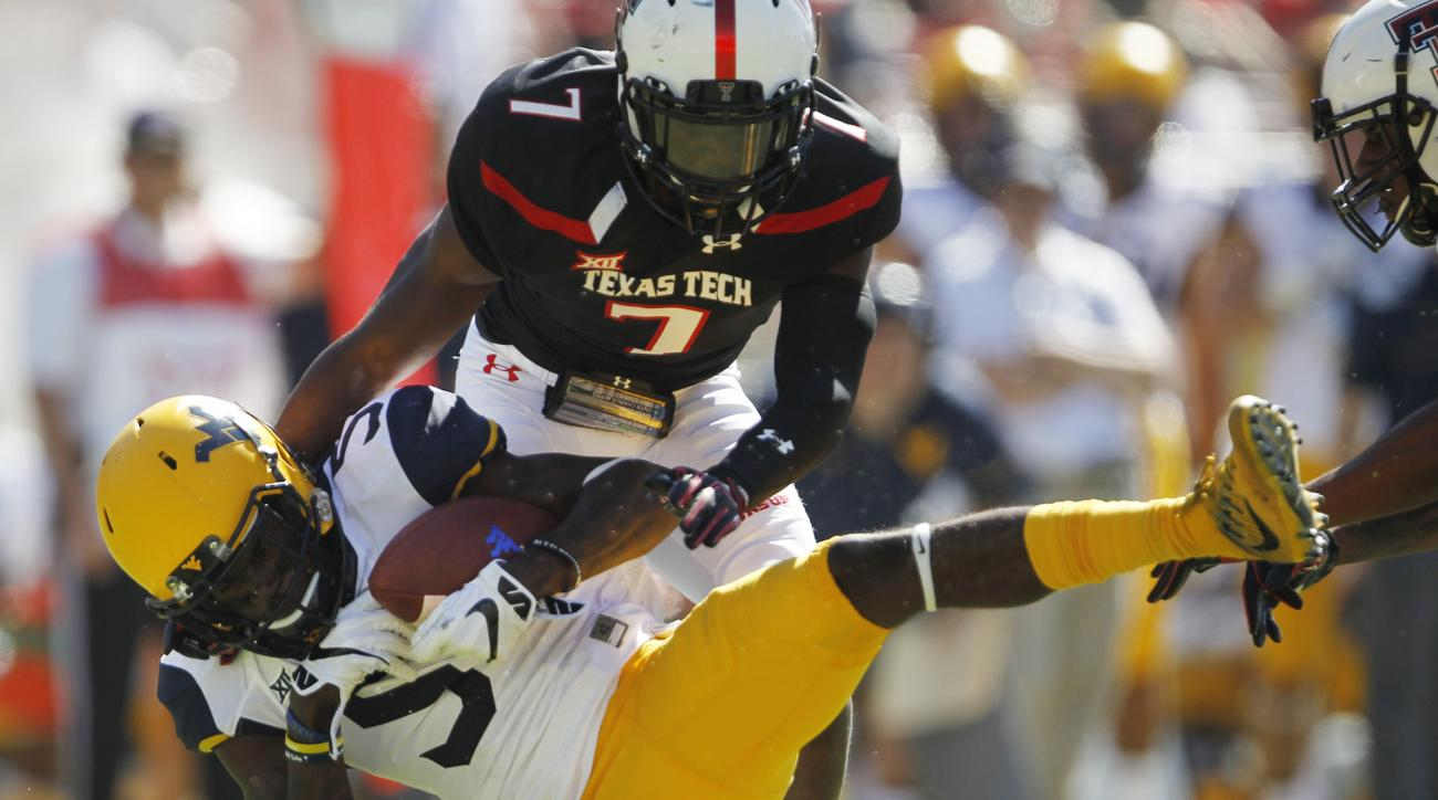FILE - In this Saturday, Oct. 15, 2016, file photo, West Virginia wide receiver Jovon Durante is tackled by Texas Tech defensive back Jah'shawn Johnson in the second quarter of an NCAA college football game at Jones AT&T Stadium in Lubbock, Texas. Durante