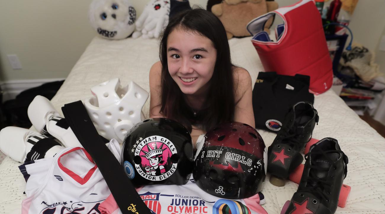 Alison Rogers poses for a photo with some of the jerseys and equipment she uses for the various sports she plays, including Tae Kwon Do and roller derby, at her home, Thursday, Oct. 27, 2016, in New York. After playing on her middle school football team l