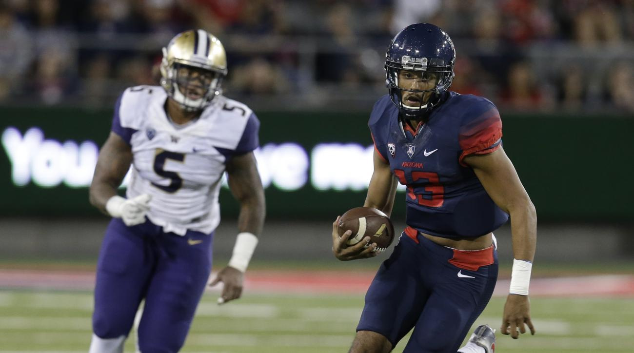 FILE  - In this Sept. 24, 2016, file photo, Arizona quarterback Brandon Dawkins (13) runs away from Washington linebacker Joe Mathis during the first half of an NCAA college football game in Tucson, Ariz. Stanford and Arizona were once teams with designs