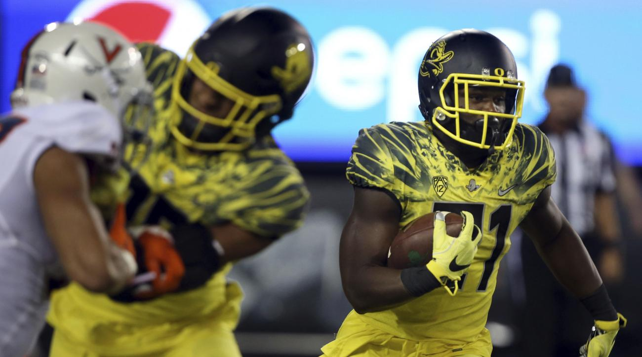 FILE - In this Sept. 10, 2016, file photo, Oregon running back Royce Freeman, right, runs against Virginia during the second half of an NCAA college football game in Eugene, Ore. With a five-game losing streak, Oregon, who plays Arizona State in Eugene, O