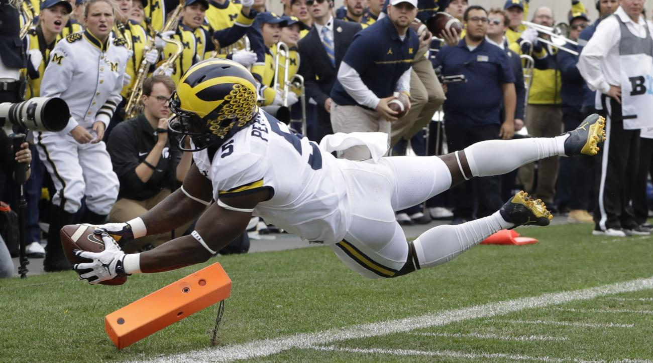 Michigan's Jabrill Peppers falls into the end zone for a touchdown during the first half of an NCAA college football game against Michigan State, Saturday, Oct. 29, 2016, in East Lansing, Mich. (AP Photo/Carlos Osorio)