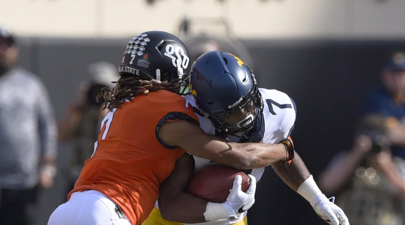 West Virginia running back Rushel Shell, center, is tackled by Oklahoma State corner back Ramon Richards, left, and safety Tre Flowers during the first half of an NCAA college football game in Stillwater, Okla., Saturday, Oct. 29, 2016. Shell, West Virgin