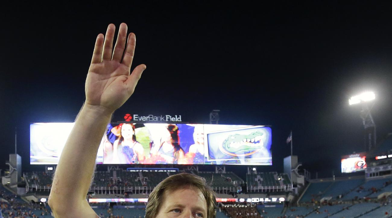 Florida head coach Jim McElwain does the Gator Chomp for fans after defeating Georgia in an NCAA college football game, Saturday, Oct. 29, 2016, in Jacksonville, Fla. (AP Photo/John Raoux)