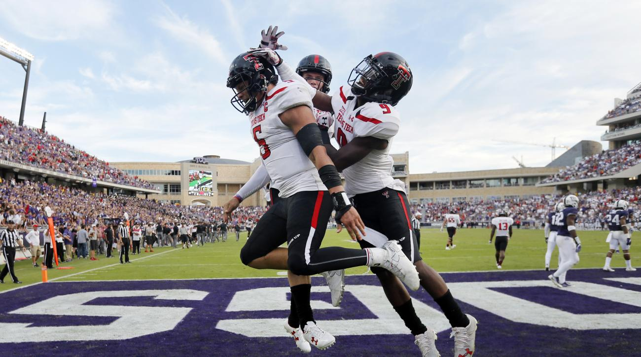 Texas Tech quarterback Patrick Mahomes II (5) celebrates his touchdown scored on a a run with wide receiver Dylan Cantrell, rear, and Jonathan Giles right, in overtime of an NCAA college football game against TCU on Saturday, Oct. 29, 2016, in Fort Worth,