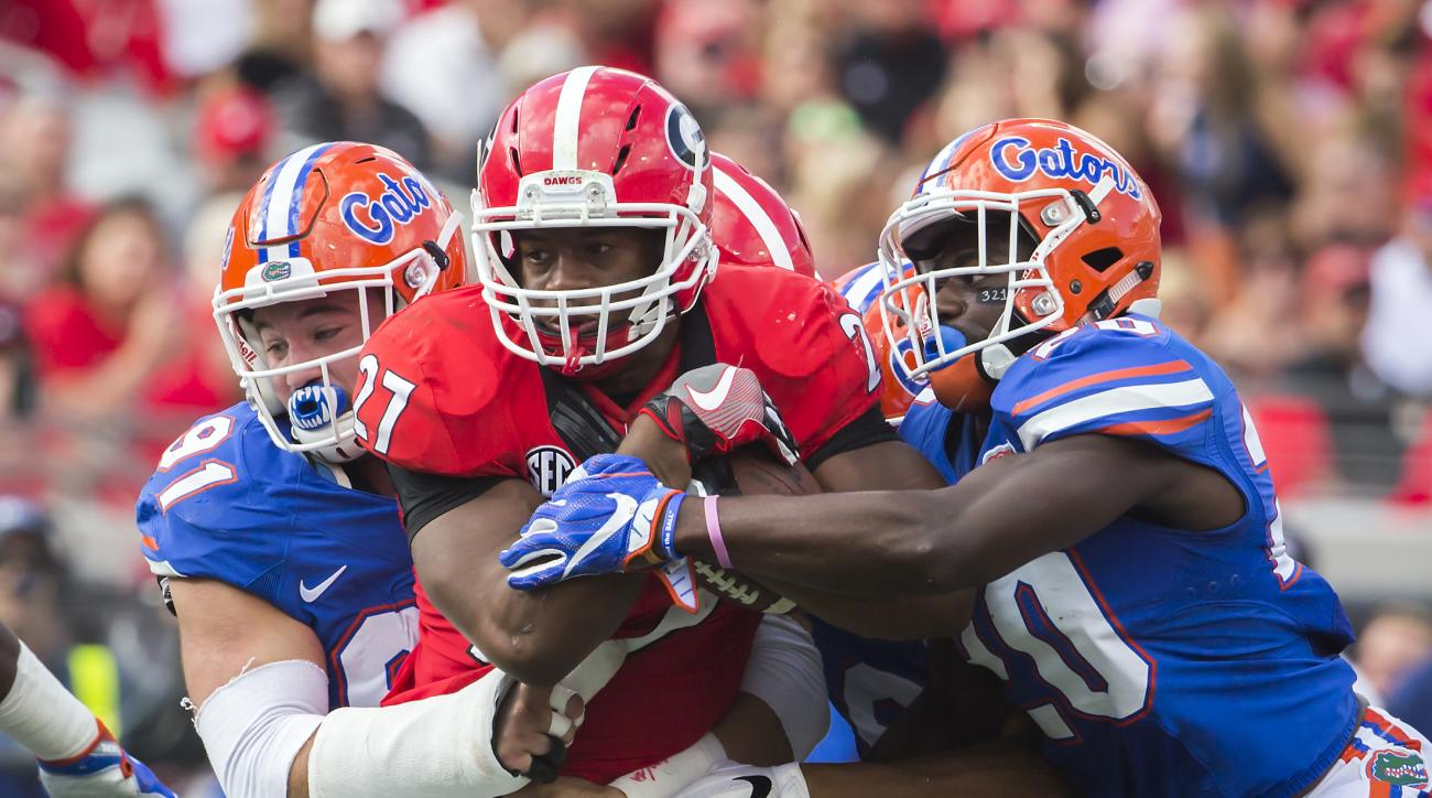 Florida defensive back Marcus Maye (20) and Florida defensive lineman Joey Ivie (91) tackle Georgia running back Nick Chubb (27) during the first half of an NCAA football game, Saturday, Oct. 29, 2016, in Jacksonville, Fla. (AP Photo/Stephen B. Morton)