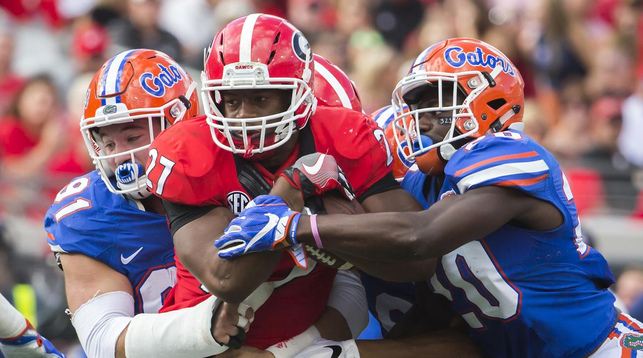 FILE - In this Saturday, Oct. 29, 2016, file photo, Florida defensive back Marcus Maye (20) and defensive lineman Joey Ivie (91) tackle Georgia running back Nick Chubb (27) during the first half of an NCAA football game in Jacksonville, Fla.  Even with ta