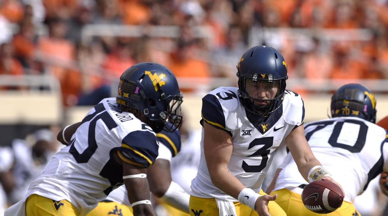 FILE - In this Saturday, Oct. 29, 2016, file photo, West Virginia quarterback Skyler Howard (3) hands off to running back Justin Crawford (25) during the first half of an NCAA college football game against Oklahoma State in Stillwater, Okla.  Oklahoma Sta