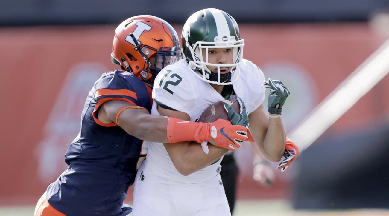 Michigan State wide receiver R.J. Shelton (12) holds on to the ball against the defense of Illinois linebacker Dele Harding (9) during the first half of an NCAA college football game at Memorial Stadium, Saturday, Nov. 5, 2016, in Champaign, Ill. (AP Phot