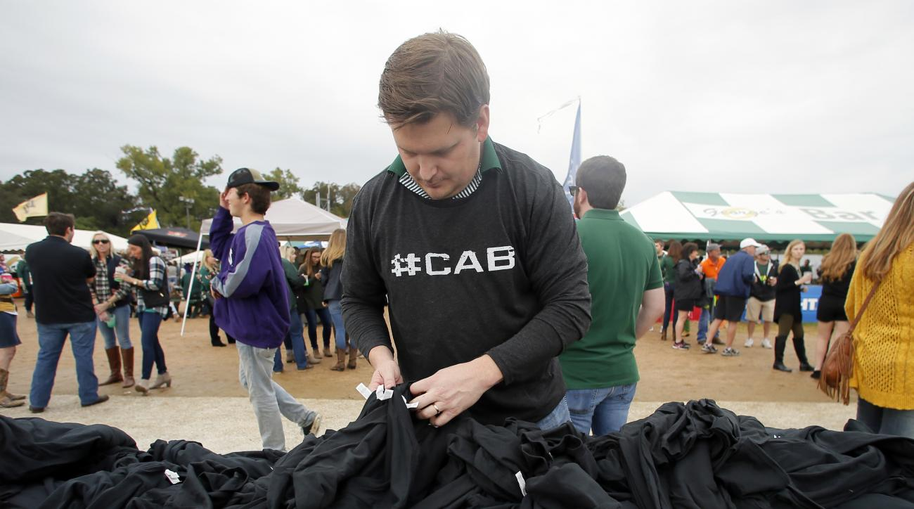 Jon McClellan of Houston surfs through a mound of shirts searching for a certain size before an NCAA college football game between TCU and Baylor on Saturday, Nov. 5, 2016, in Waco, Texas. The shirt has the word #CAB printed on them, and stands for Coach