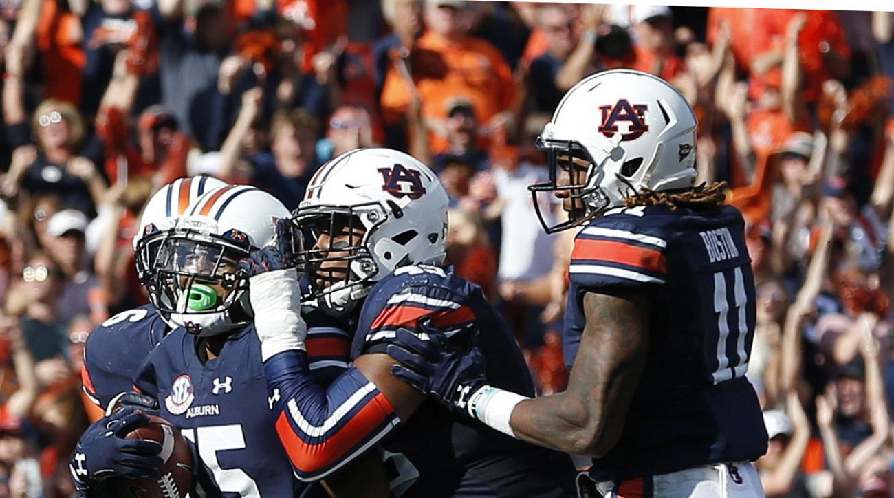 Auburn defensive back Joshua Holsey (5) celebrates with teammates after intercepting a pass against Vanderbilt during the second half of an NCAA college football game, Saturday, Nov. 5, 2016, in Auburn, Ala. (AP Photo/Brynn Anderson)