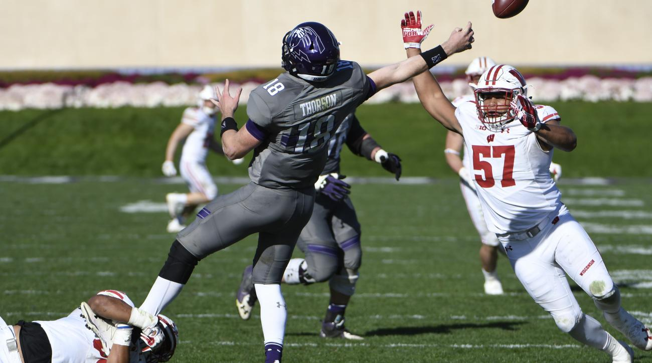 Wisconsin linebacker T.J. Edwards, left, grabs Northwestern quarterback Clayton Thorson (18) by the leg as linebacker defensive end Alec James (57) pressures during the second half of an NCAA college football game in Evanston, Ill., Saturday, Nov. 5, 2016