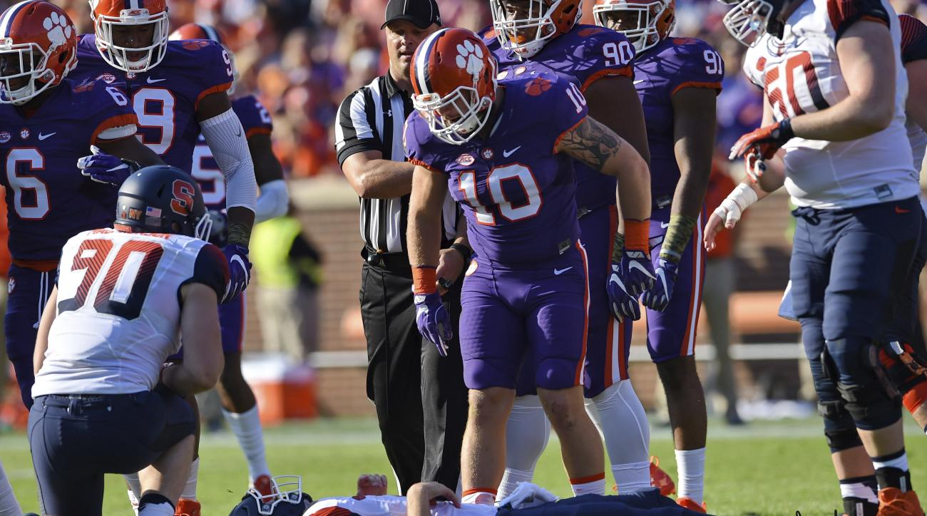 Clemson's Ben Boulware (10) stands over Syracuse quarterback Eric Dungey after making a tackle during the first half of an NCAA college football game Saturday, Nov. 5, 2016, in Clemson, S.C. Dungey left the game due to injuries. (AP Photo/Richard Shiro)