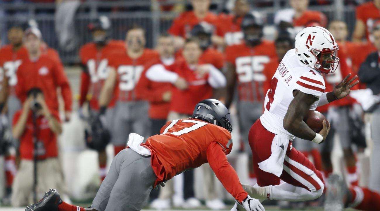 Nebraska quarterback Tommy Armstrong, right, is chased by Ohio State linebacker Jerome Baker during the first half of an NCAA college football game Saturday, Nov. 5, 2016, in Columbus, Ohio. Armstrong was injured on the play and left the stadium in an amb