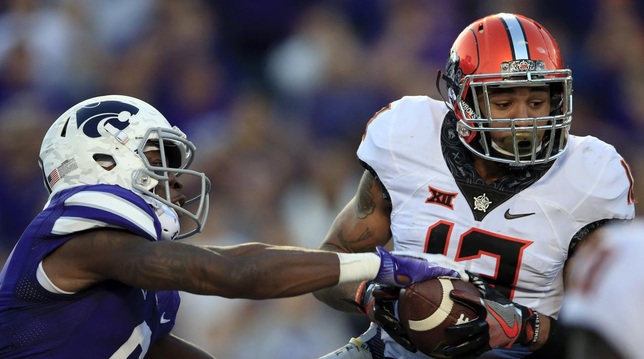 FILe - In this Nov. 5, 2016, file photo, Oklahoma State linebacker Jordan Sterns (13), right, intercepts, in the end zone, a pass intended for Kansas State wide receiver Deante Burton (6) on the last play of the game in the second half of an NCAA college