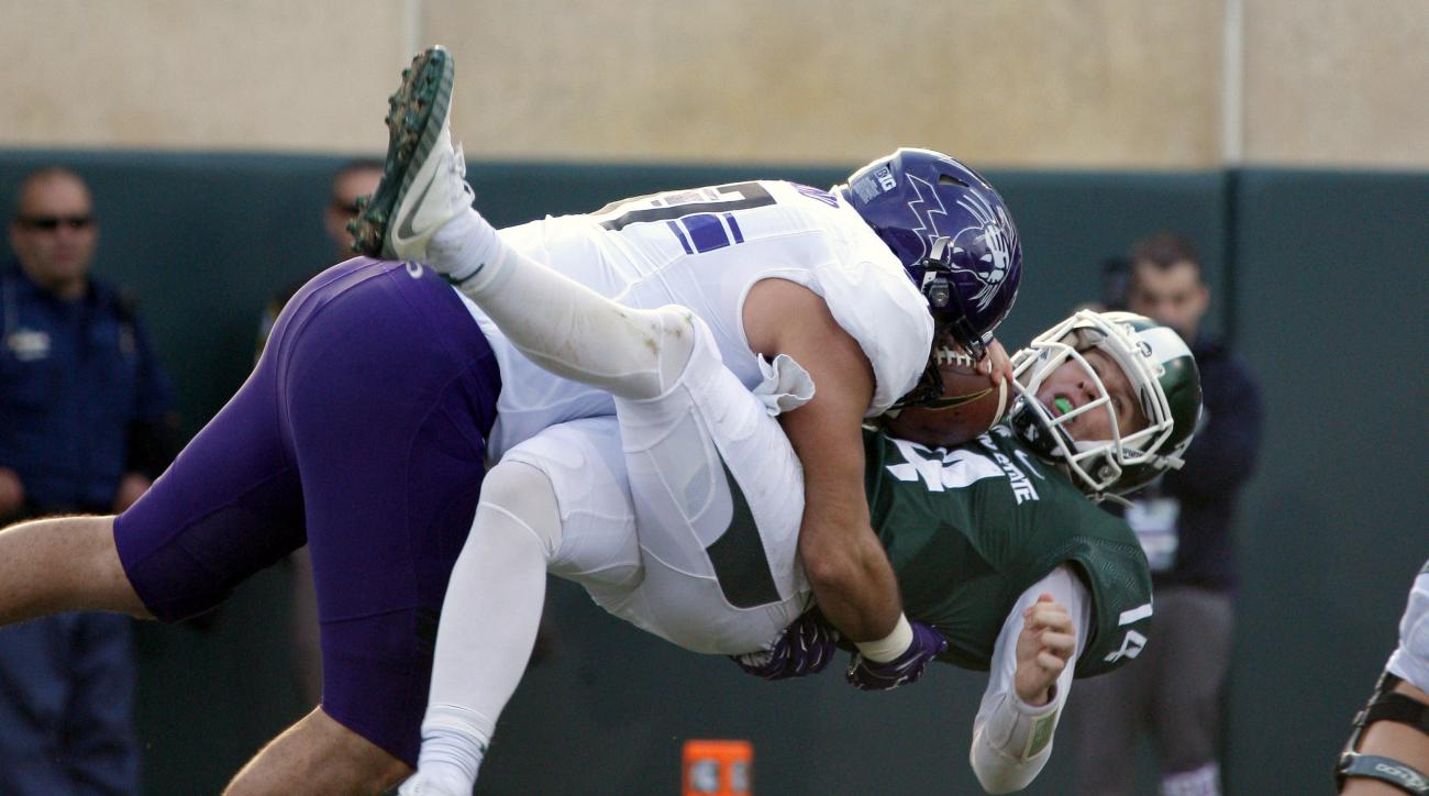 FILE - In this Oct. 15, 2016, file photo, Northwestern's Joe Gaziano, left, sacks Michigan State quarterback Brian Lewerke for a safety during the second quarter of an NCAA college football game, in East Lansing, Mich. The fall of Michigan State could end