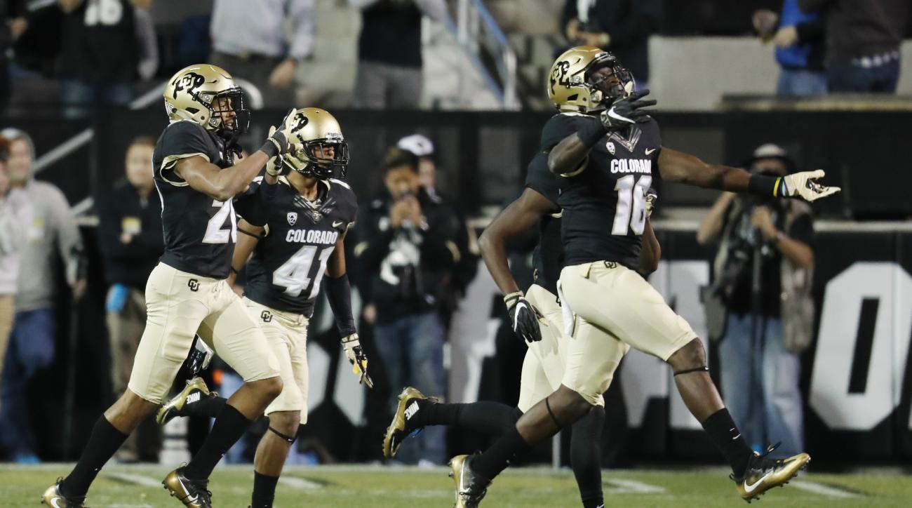 In this Thursday, Nov. 3, 2016, photo, Colorado special teams player Jaleel Awini, front right, celebrates after punt returner Isaiah Oliver, back, right, scored a touchdown on the kick as special teams players Kyle Evans, front left, and Andrew Bergner f