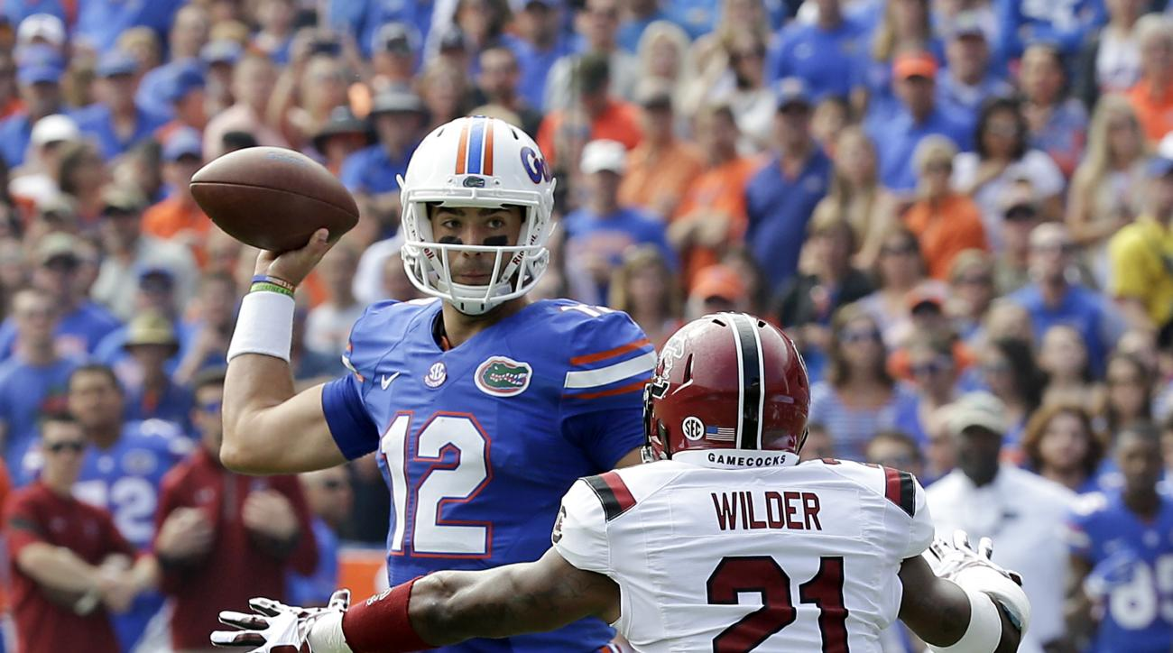 Florida quarterback Austin Appleby (12) looks for a receiver as he is pressured by South Carolina defensive back Antoine Wilder (21) during the first half of an NCAA college football game, Saturday, Nov. 12, 2016, in Gainesville, Fla. (AP Photo/John Raoux