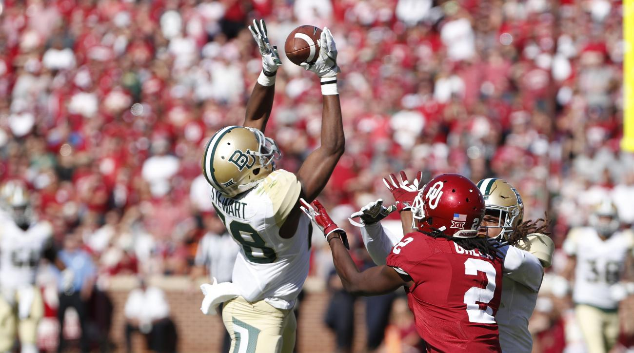 Baylor safety Orion Stewart (28) makes an interception ahead of Oklahoma wide receiver Dahu Green (2) during the first half of an NCAA college football game in Norman, Okla. on Saturday, Nov. 12, 2016. (AP Photo/Alonzo Adams)