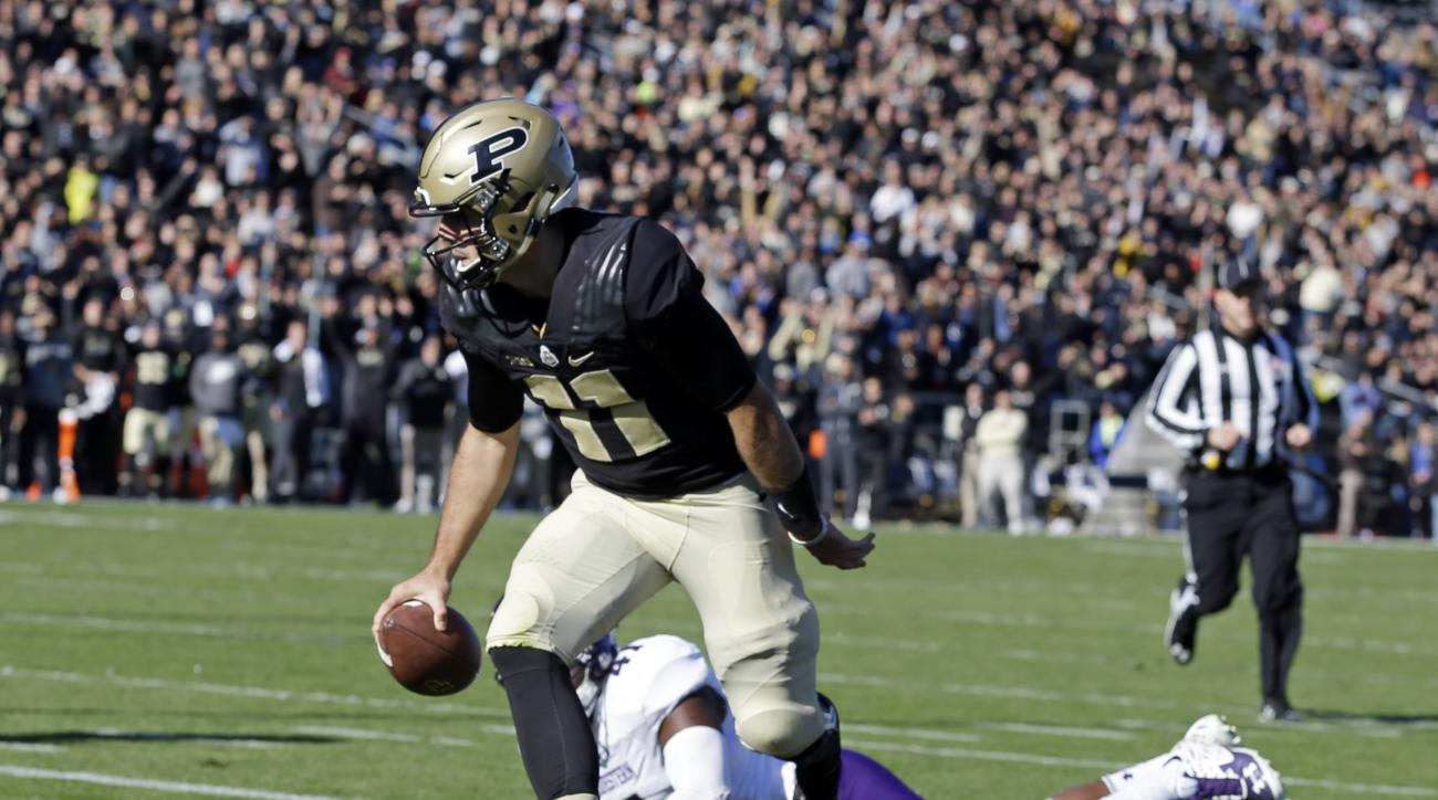 Purdue quarterback David Blough (11) scores a touchdown after getting past Northwestern safety Jared McGee (41) during the first half of an NCAA college football game in West Lafayette, Ind., Saturday, Nov. 12, 2016. (AP Photo/Michael Conroy)
