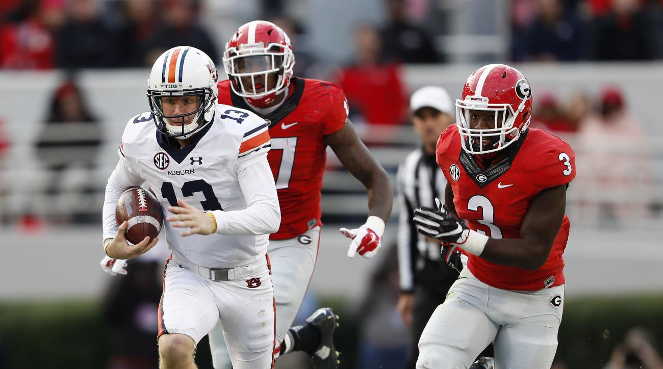 Auburn quarterback Sean White (13) breaks away fro Georgia linebackers Davin Bellamy (17) and Roquan Smith (3) in the first half of an NCAA college football game Saturday, Nov. 12, 2016, in Athens, Ga. (AP Photo/John Bazemore)