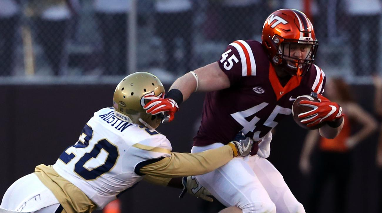 Virginia Tech fullback Sam Rogers (45) tries to escape the tackle of Georgia Tech defender Lawrence Austin (20) during the first half of an NCAA football game in Blacksburg, Va., Saturday, Nov. 12 2016. (Matt Gentry/The Roanoke Times via AP)