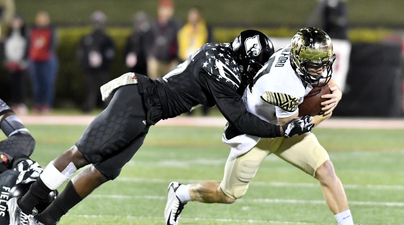 Wake Forest's John Wolford (10) is tackled by Louisville's Stacy Thomas (32) during the first halfof an NCAA college football game, Saturday, Nov. 12, 2016, in Louisville, Ky. (AP Photo/Timothy D. Easley)