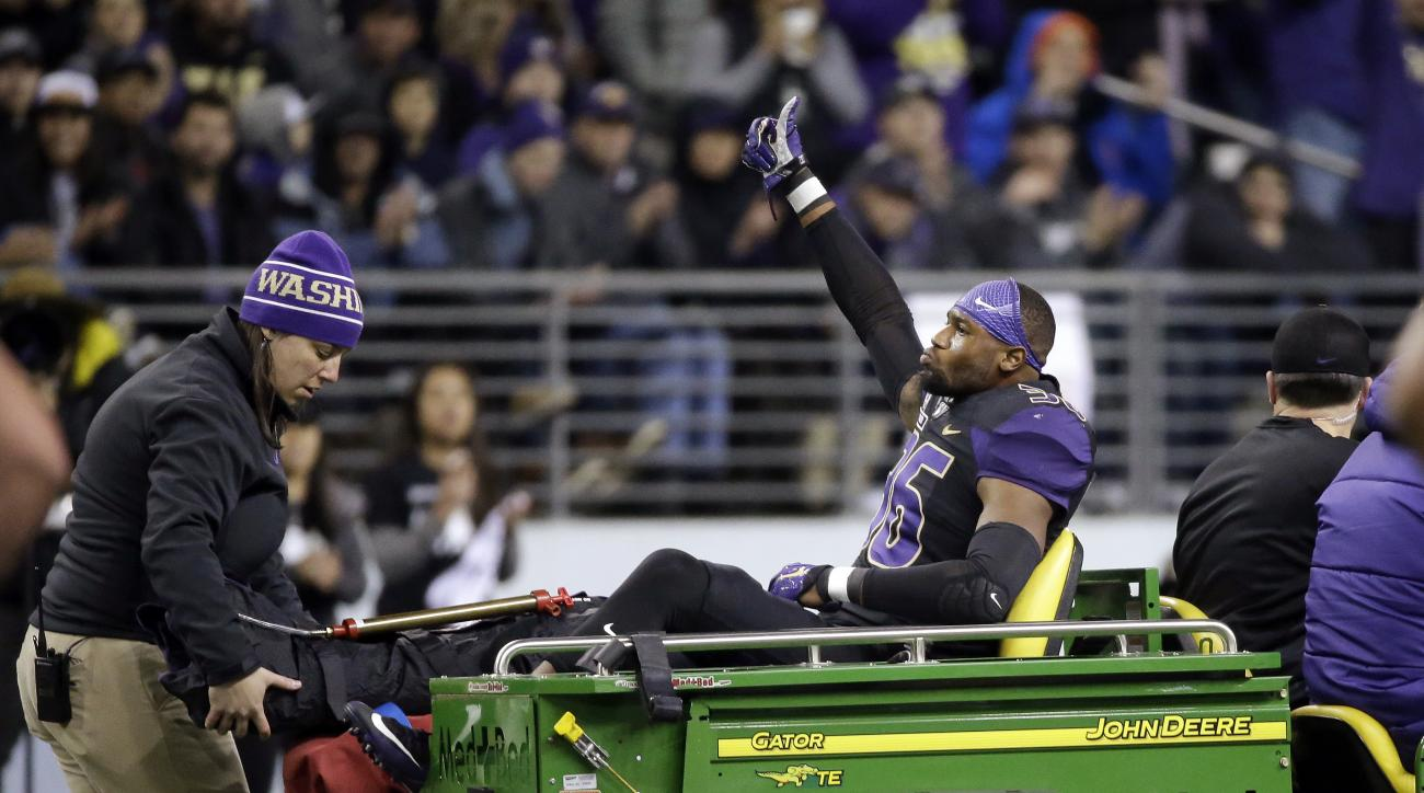 Washington linebacker Azeem Victor gives a thumbs-up as he leaves the field in a cart after being injured against Southern California in the first half of an NCAA college football game Saturday, Nov. 12, 2016, in Seattle. (AP Photo/Elaine Thompson)