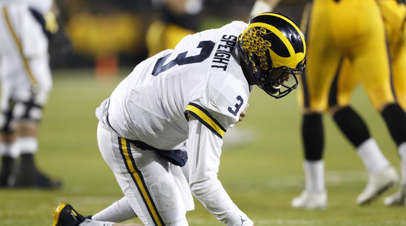 Michigan quarterback Wilton Speight kneels on the turf after getting hit during the second half of the team's NCAA college football game against Iowa, Saturday, Nov. 12, 2016, in Iowa City, Iowa. Iowa won 14-13. (AP Photo/Charlie Neibergall)