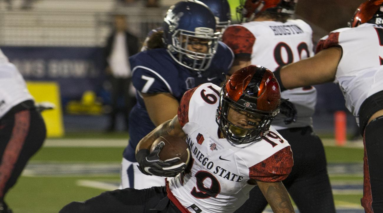 San Diego State running back Donnel Pumphrey is hit by Nevada's Elijah Mitchell during the first half of an NCAA college football game Saturday, Nov. 12, 2016 in Reno, Nev. (AP Photo/Tom R. Smedes)
