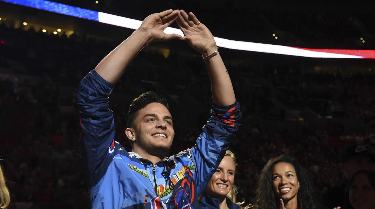 Devon Allen, a University of Oregon football player who competed in the hurdles at the Olympics, acknowledges the crowd during a ceremony honoring Olympians from the state of Oregon, at halftime of an NBA basketball game between the Portland Trail Blazers