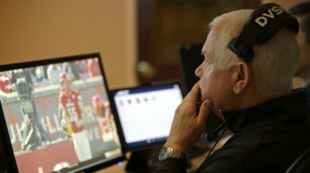 In this photo taken Saturday, Oct. 22, 2016, Ralph Pickett, the collaborative replay official, watches a game in the replay room at the Atlantic Coast Conference headquarters in Greensboro, N.C. The Atlantic Coast, Southeastern and Pac-12 conferences are