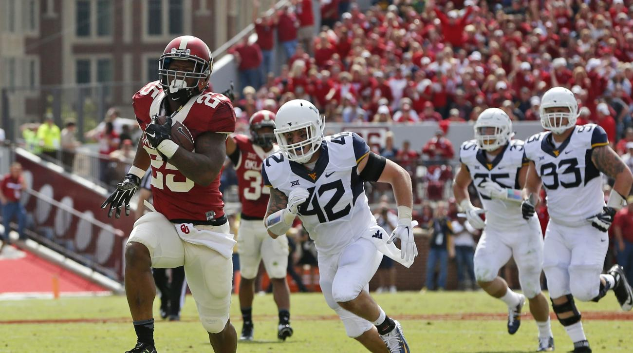 FILE - In this Oct. 3, 2015, file photo, Oklahoma running back Joe Mixon (25) runs for a touchdown against West Virginia during an NCAA college football game in Norman, Okla. Oklahoma and West Virginia meet again on Saturday, Nov. 19. Since joining the Bi