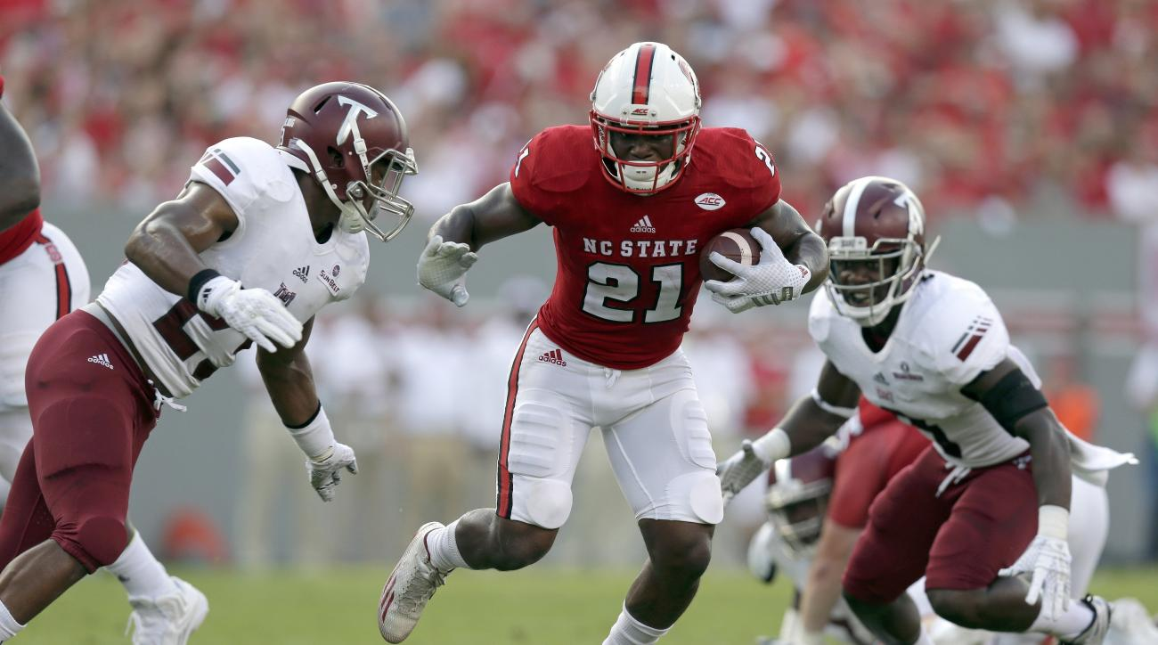 FILE - In this Sept. 5, 2015, file photo, North Carolina State's Matt Dayes (21) finds some running room as Troy's William Lloyd, left, moves in for the tackle during an NCAA college football game in Raleigh, N.C. Dayes can become the first Wolfpack playe