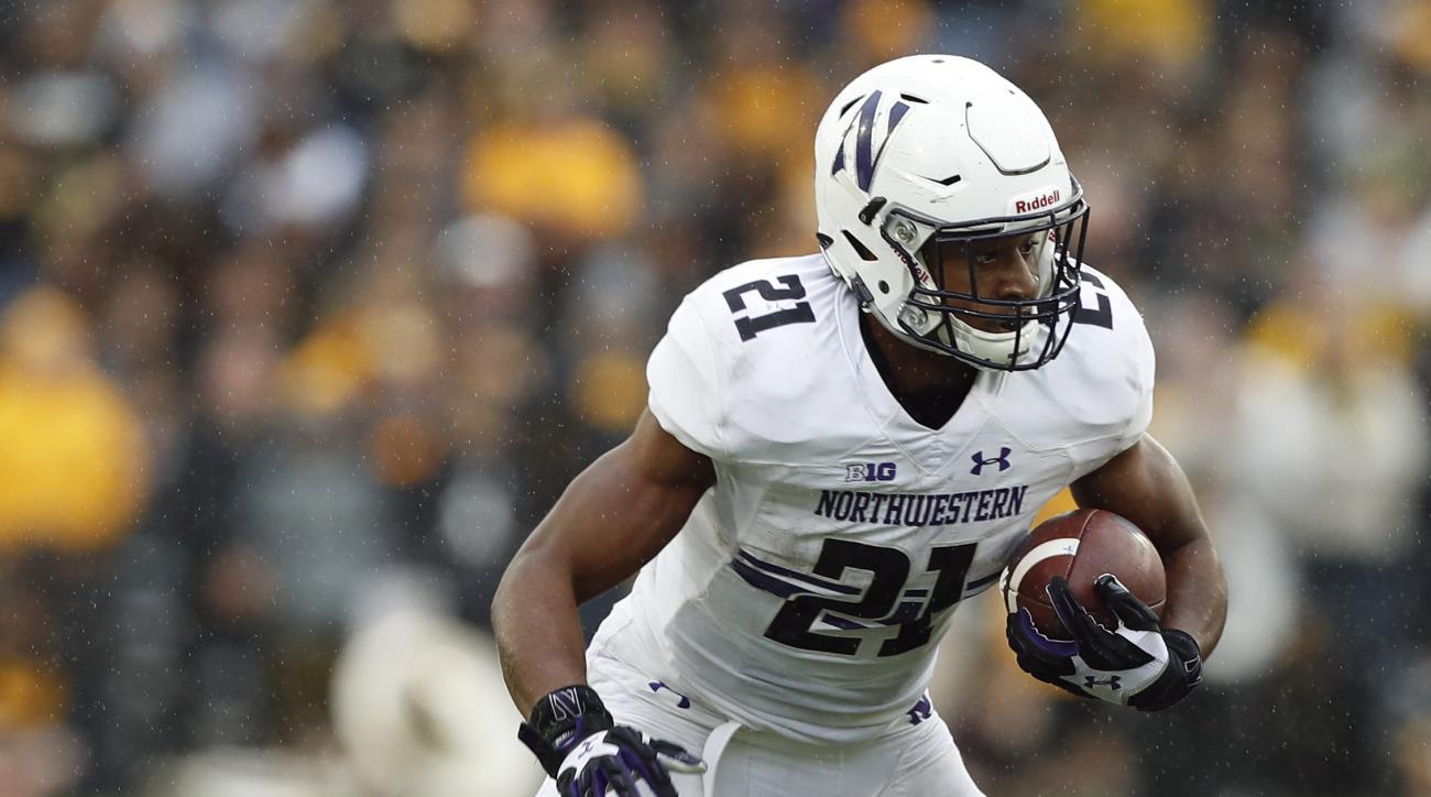 FILe - In this Oct. 1, 2016, file photo, Northwestern running back Justin Jackson (21) breaks a tackle by Iowa defensive back Greg Mabin (13) during the second half of an NCAA college football game, in Iowa City, Iowa. Minnesota's senior class, with the m
