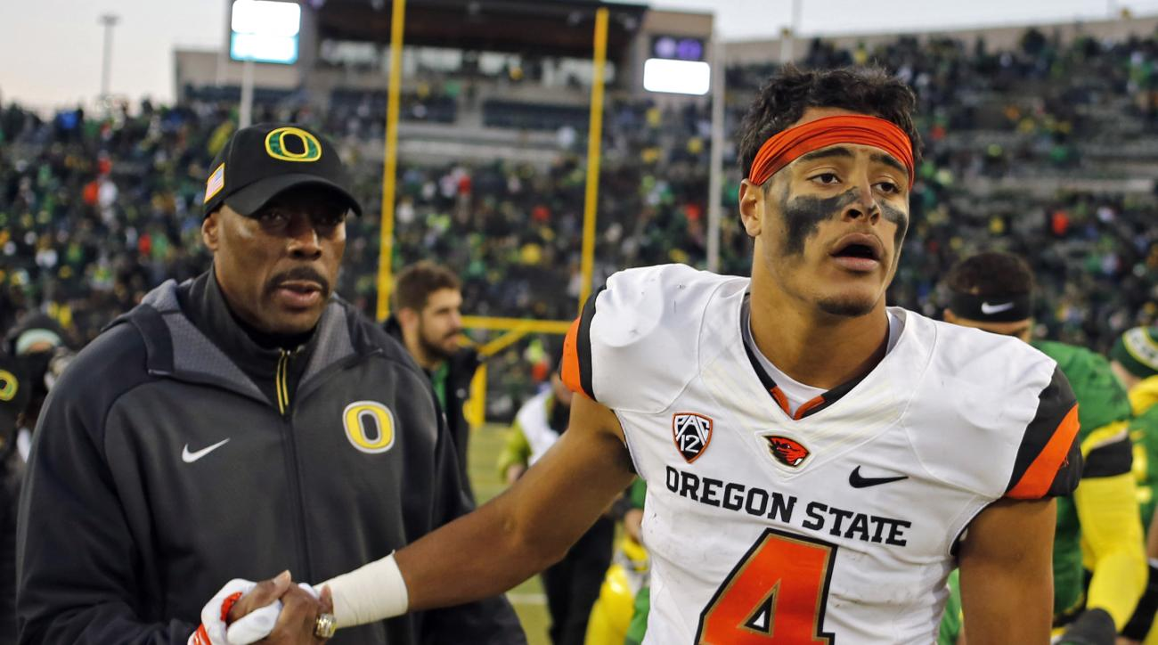 FILE - In this Nov. 27, 2015, file photo, Oregon State's Seth Collins, right, shakes hands with Oregon defensive coordinator Don Pellum after an NCAA college football game in Eugene Ore. Heading into the final two games of the season, Oregon State was dea