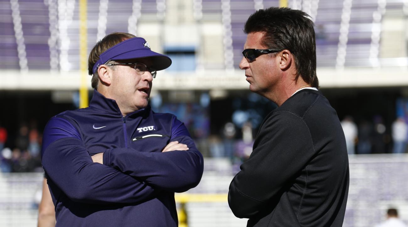 TCU head coach Gary Patterson and Oklahoma State head coach Mike Gundy talk before an NCAA college football game, Saturday, Nov. 19, 2016, in Fort Worth, Texas. (AP Photo/Jim Cowsert)