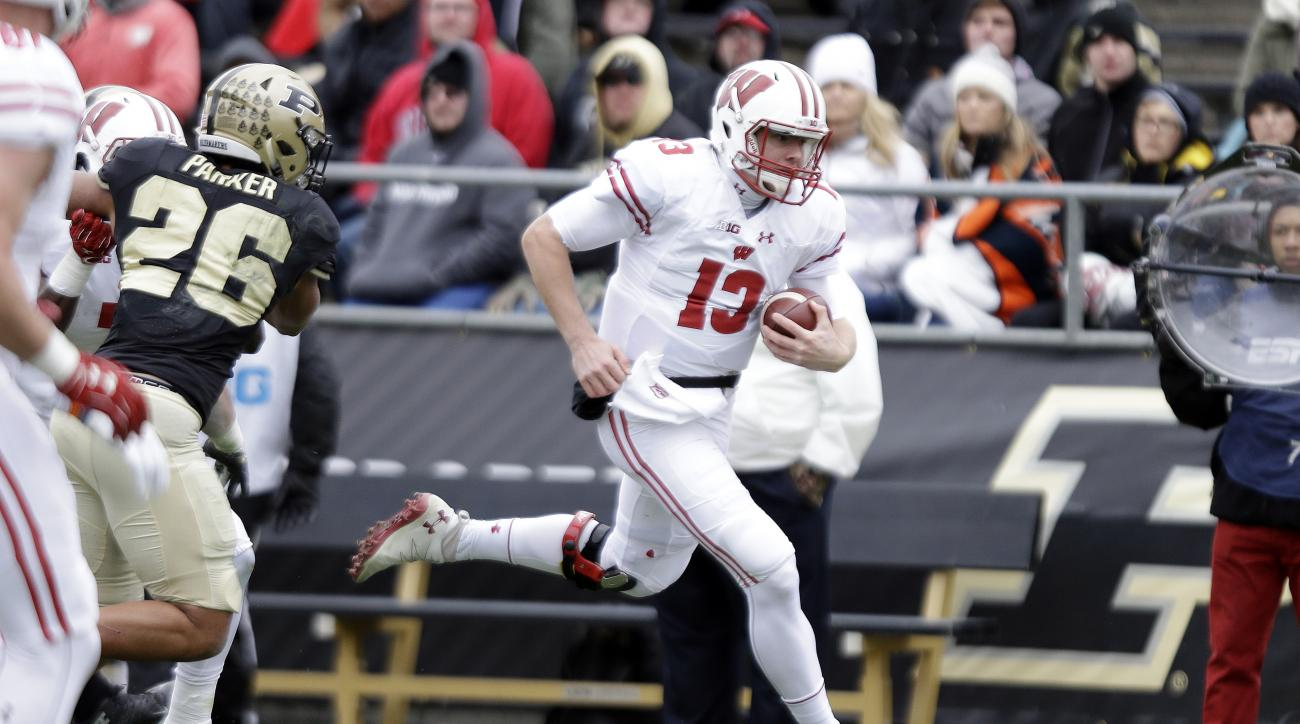 Wisconsin quarterback Bart Houston (13) runs past Purdue safety C.J. Parker (26) during the first half of an NCAA college football game in West Lafayette, Ind., Saturday, Nov. 19, 2016. (AP Photo/Michael Conroy)