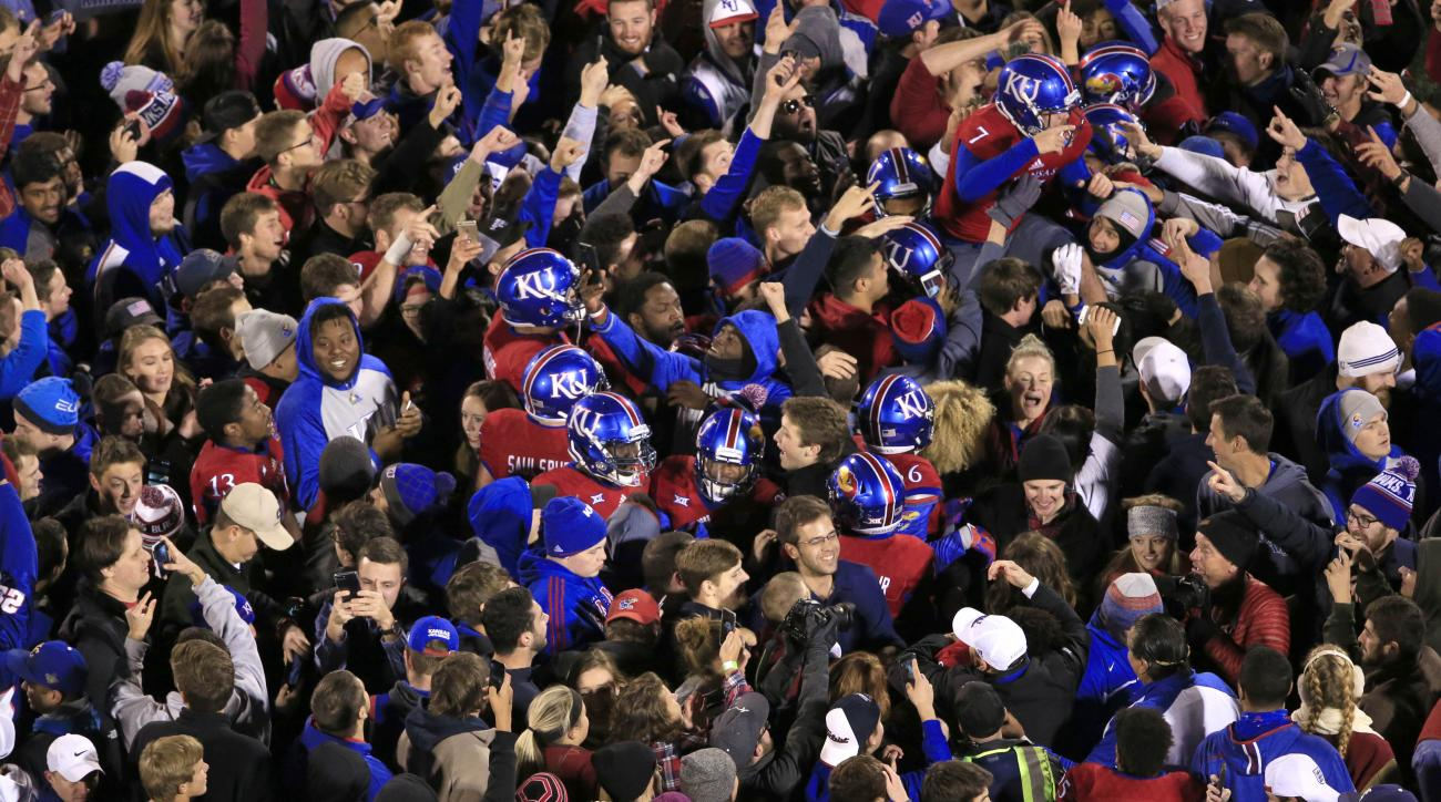 Kansas players and fans celebrate after defeating Texas in overtime of an NCAA college football game in Lawrence, Kan., Saturday, Nov. 19, 2016. Kansas defeated Texas 24-21. (AP Photo/Orlin Wagner)