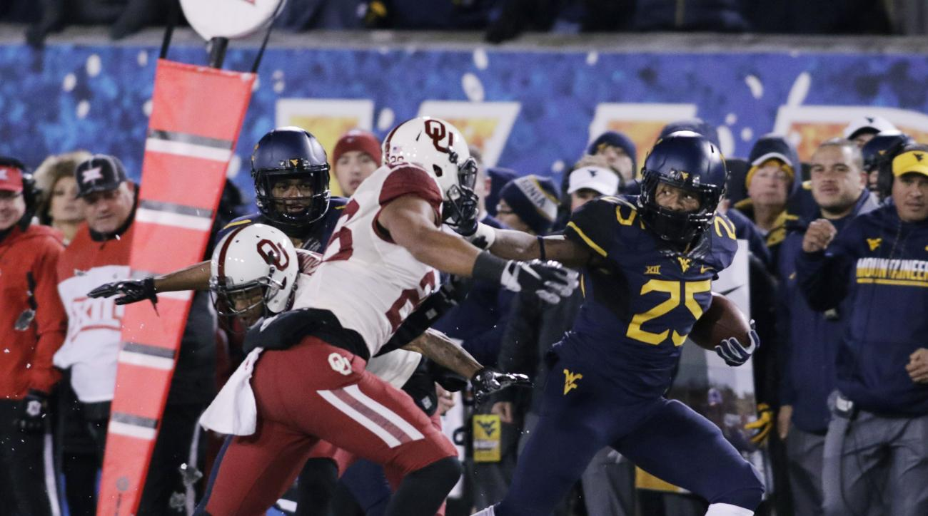 West Virginia running back Justin Crawford (25) breaks away from Oklahoma linebacker Jordan Evans (26) during the first half of an NCAA college football game, Saturday, Nov. 19, 2016, in Morgantown, W.Va. (AP Photo/Raymond Thompson)