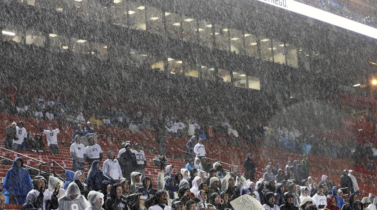 Fans, most of them for Penn State, stand in hail and rain as they cheer during the second half of an NCAA college football game between Penn State and Rutgers on Saturday, Nov. 19, 2016, in Piscataway, N.J. Penn State won 39-0. (AP Photo/Mel Evans)
