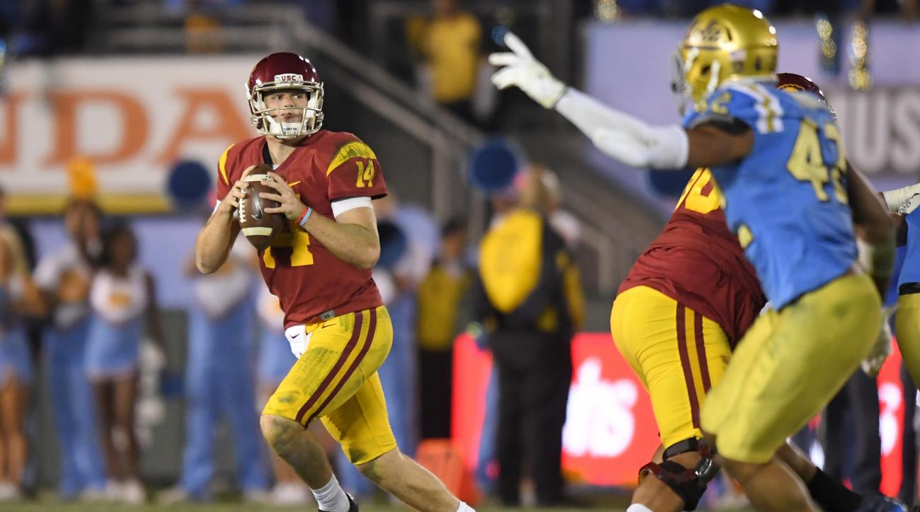Southern California quarterback Sam Darnold, left, rolls out to pass while under pressure from UCLA linebacker Kenny Young during the second half of an NCAA college football game, Saturday, Nov. 19, 2016, in Pasadena, Calif. Southern California won 36-14.