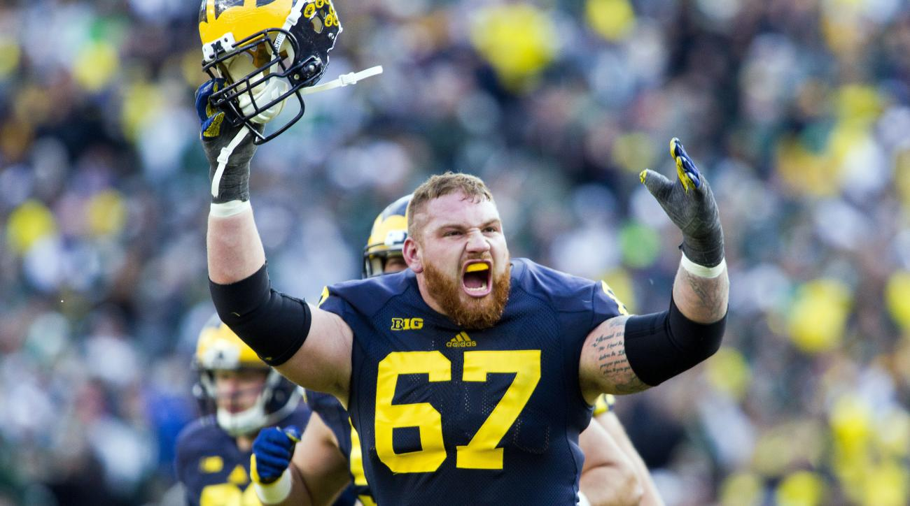 FILE - In this Oct. 17, 2015, file photo, Michigan offensive lineman Kyle Kalis (67) celebrates a ruling confirming a Michigan touchdown after it was reviewed, in the third quarter of an NCAA college football game against Michigan State, in Ann Arbor, Mic
