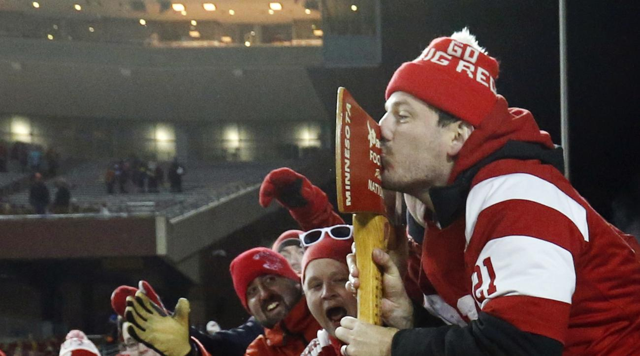 FILE - In this Nov. 28, 2015, file p;hoto, a Wisconsin fan kisses the prized Paul Bunyan axe carried by Wisconsin offensive lineman Tyler Marz (61) after Wisconsin beat Minnesota 31-21 in an NCAA college football game, in Minneapolis. At some point this w