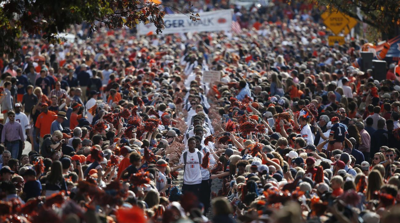 FILE - In this Nov. 28, 2015, file photo, Auburn football players high five fans during the Tiger Walk before the first half of an NCAA college football game against Alabama, in Auburn, Ala. The top-ranked Crimson Tide and No. 16 Auburn meet Saturday in T