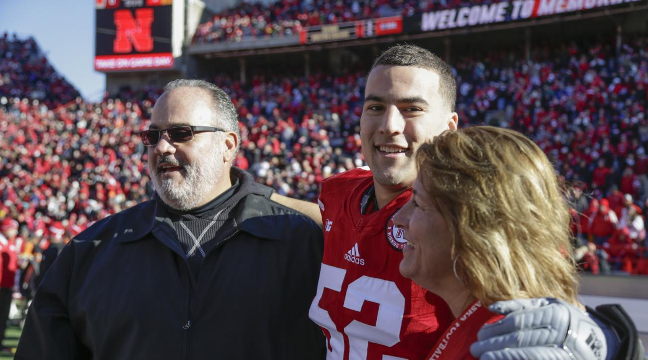 In this Nov. 19, 2016 photo, Nebraska linebacker Josh Banderas (52), stands with his father Tom and mother Amy during Senior Day activities before an NCAA college football game against Maryland in Lincoln, Neb. Three decades after Tom Banderas was a tight